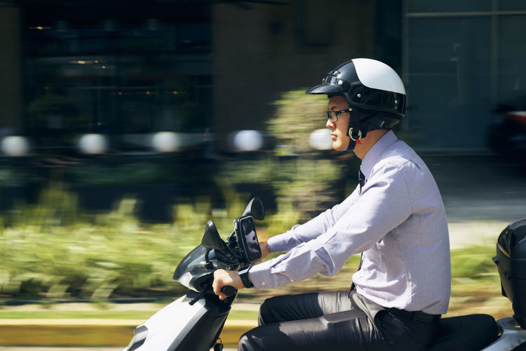 Side view of man riding motor scooter