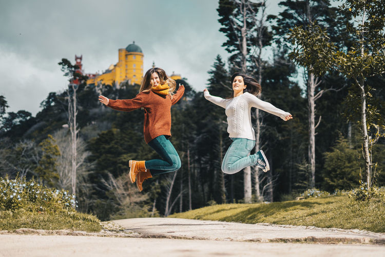 Portrait of beautiful females jumping on street against trees