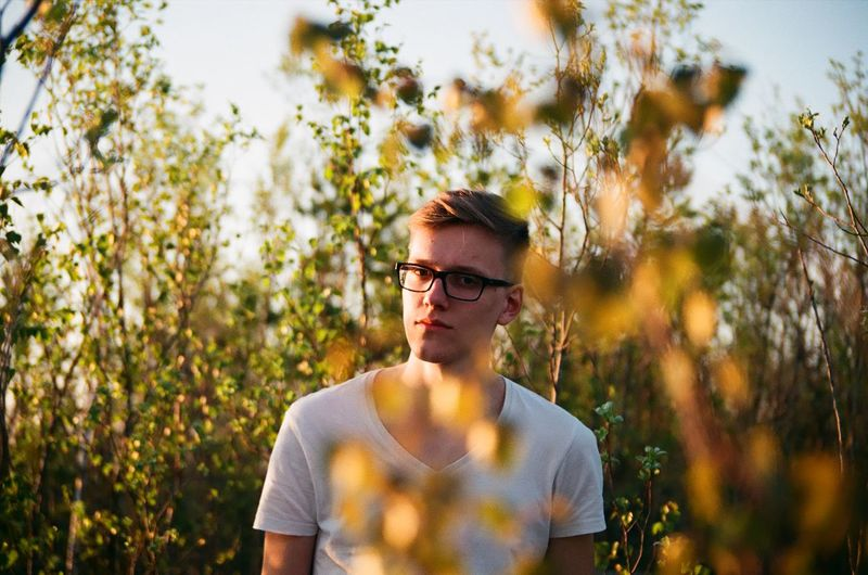 Portrait Of Young Man Amidst Plants During Sunset