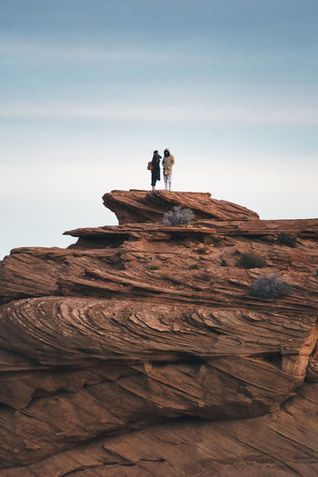 Great is the one who stands on top while being down to earth. Page Travel Destinations Travelers Travel On Top On Top Of The World Relationship Couple Goals Couple People Standing Nature Outdoors Tranquil Scene Tranquility Beauty In Nature Rock Formation Scenics - Nature Leisure Activity Men Real People Rock - Object Solid Rock Sky Moments Of Happiness 2018 In One Photograph