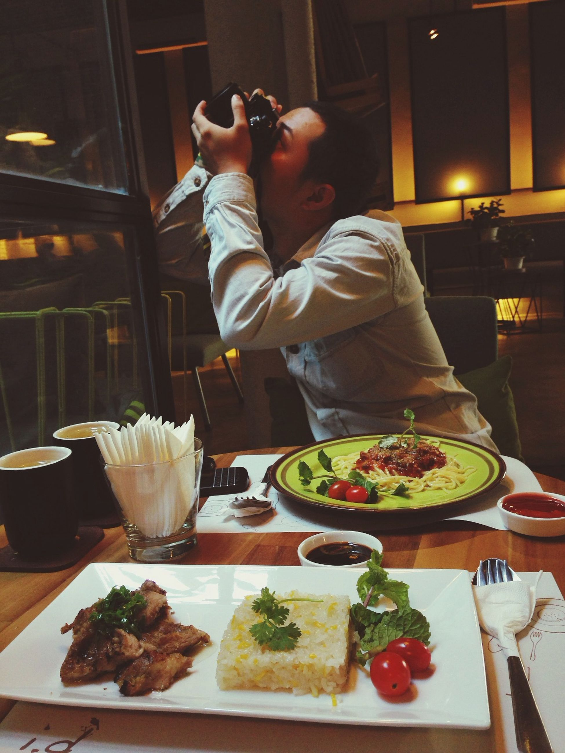 food and drink, food, indoors, men, lifestyles, freshness, standing, leisure activity, person, casual clothing, sitting, table, healthy eating, holding, vegetable, preparation, restaurant