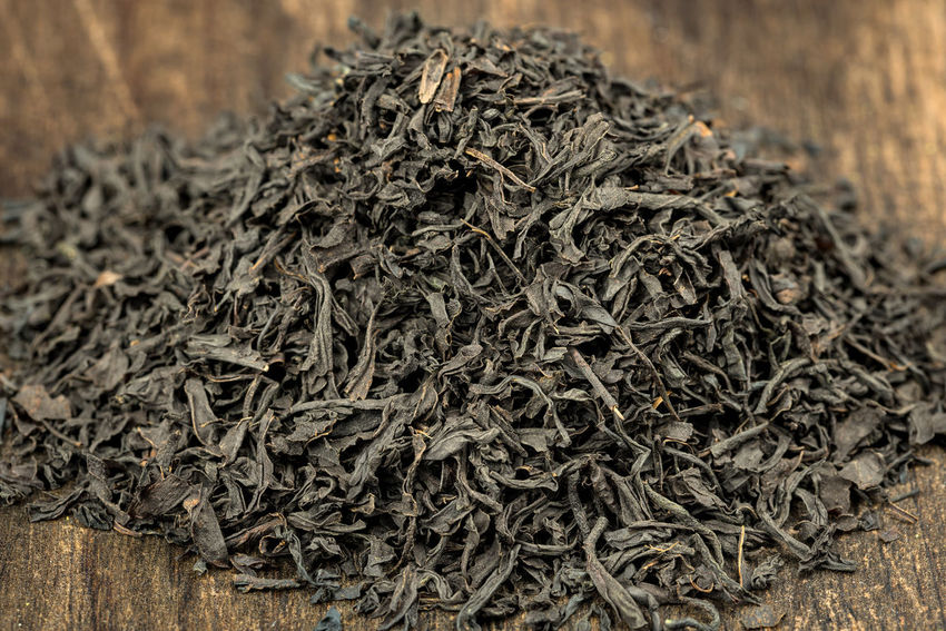 Green or black tea leaves on wooden plate or background Aroma; Aromatic; Asia; Asian; Basket; Beverage; Chinese; Culture; Drink; Dry; Drying; Fragrance; Green; Green Tea; Harvest; Leaf; Leaves; Macro; Organic; Plant; Process; Roast; Tea; Traditional; Wood;