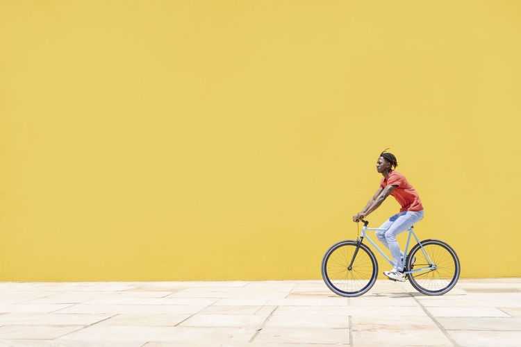 Woman riding bicycle against yellow wall