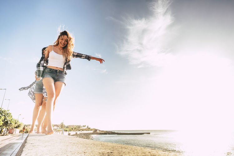 Group of three girls walking on a wall near the beach Adult Beach Beautiful People Beautiful Woman Beauty In Nature Carefree Cheerful Enjoyment Freedom Fun Happiness Leisure Activity Nature Only Women Outdoors Sea Sky Smiling Standing Summer Vacations Vitality Water Young Adult Young Women
