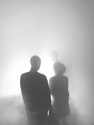 Rear view of man and woman standing in fog