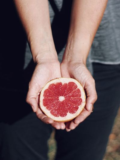 Midsection Of Person Holding Grapefruit