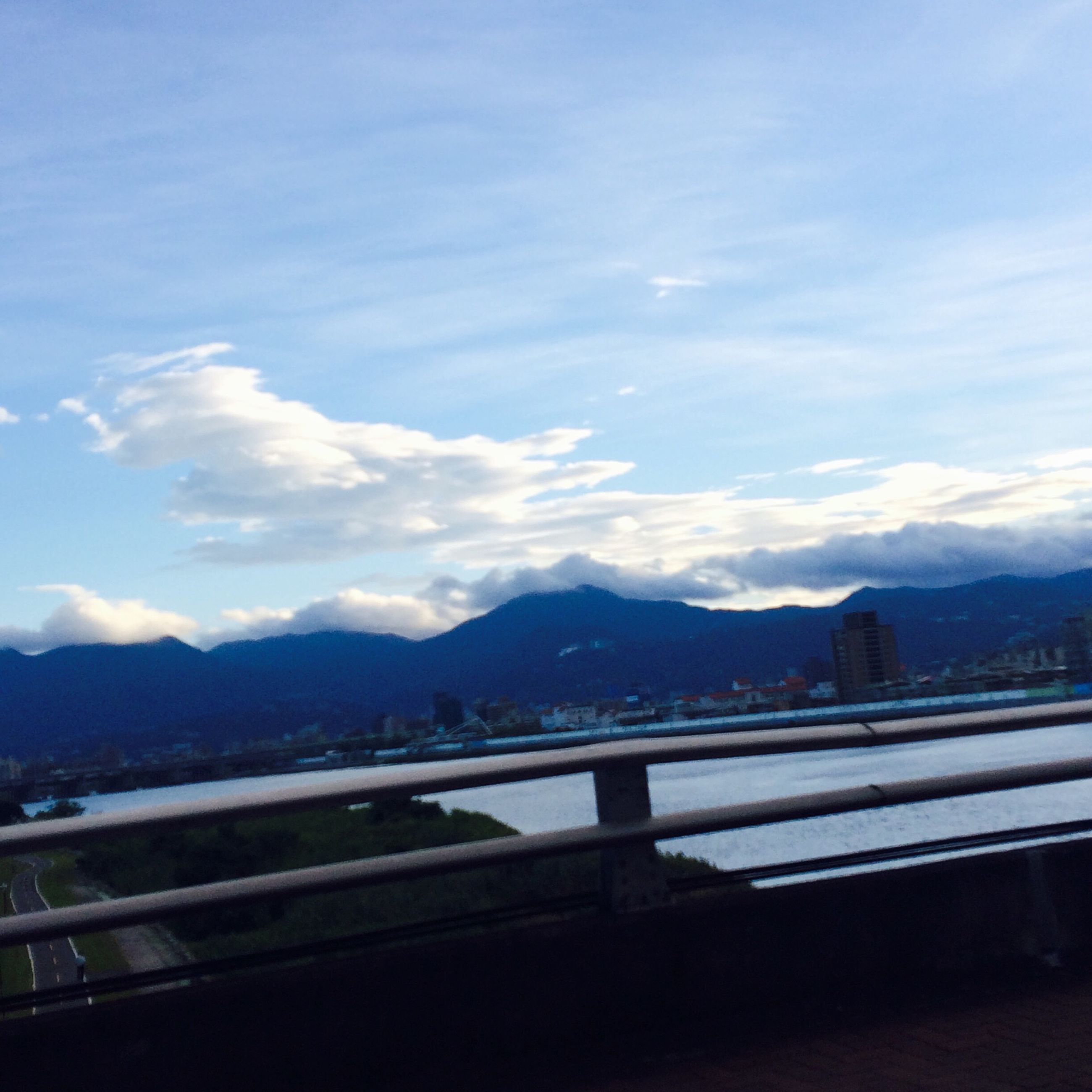 mountain, mountain range, sky, water, railing, cloud - sky, built structure, river, architecture, cloud, scenics, nature, building exterior, beauty in nature, tranquil scene, lake, transportation, city, tranquility, cloudy