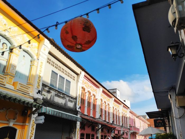 Low angle view of lanterns hanging by buildings against sky