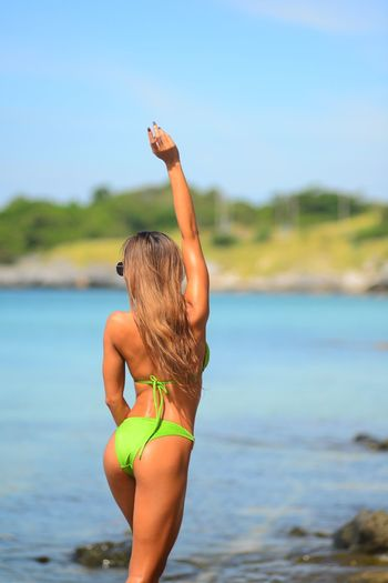 Rear view of young woman wearing bikini while standing at beach