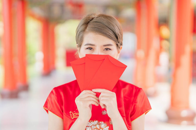 Close-up portrait of girl holding red umbrella