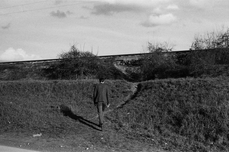 a man walking Street Blackandwhite Outdoor Photography Focus On Foreground Portrait Streetphotography EyeEm Best Shots Analog Portrait Photography EyeEmNewHere Outdoors EyeEm Selects Lifestyles 35mm Film Moody Clothing Film Photography Film Ilford Industrial Tree Sky FootPrint Sand Dune Tranquility Countryside Calm Scenics