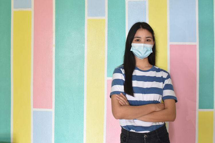 Portrait of young woman standing against multi colored wall