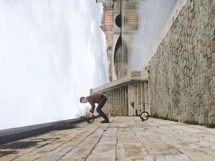 Tilt Image Of Man Climbing Wall Against Lake