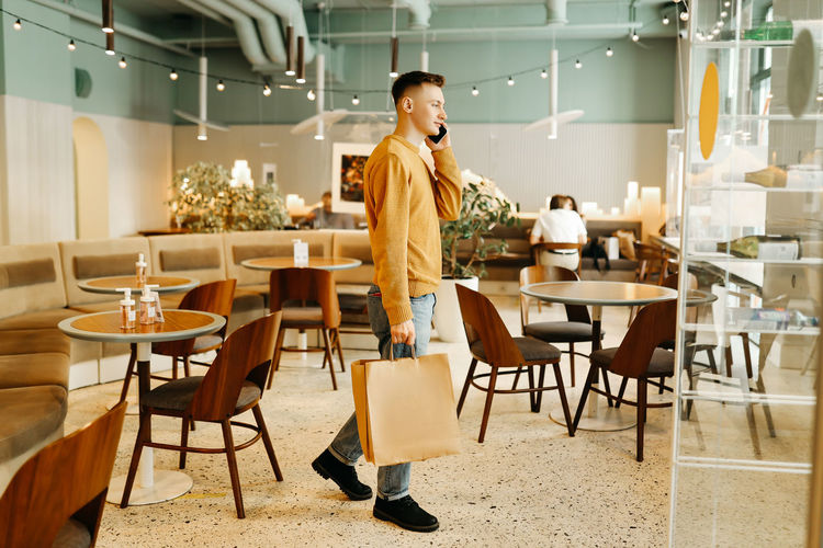 A young man in casual clothes with bags in his hands after shopping stands alone and talks in a cafe