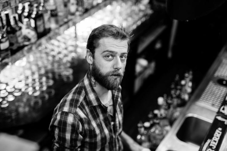 High angle portrait of bartender working in bar
