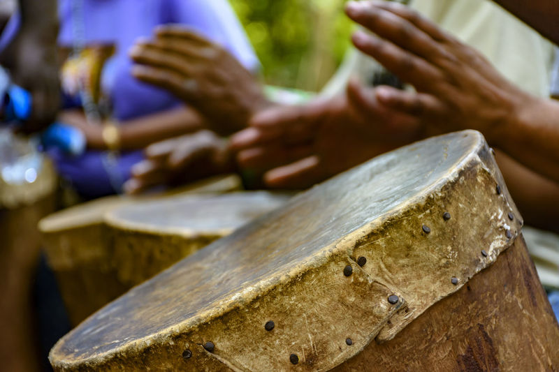 Cropped hands of people playing old drum outdoors