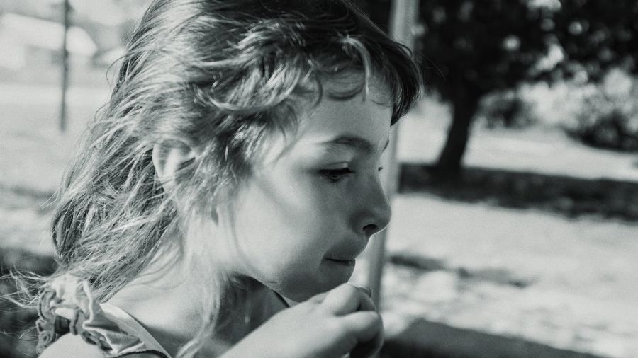 Close-up of thoughtful girl standing outdoors
