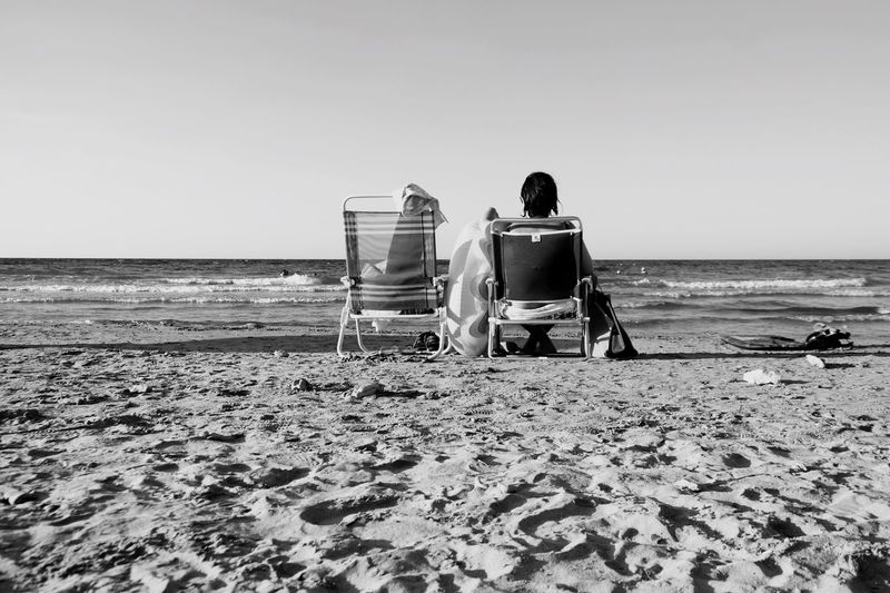 Rear view of person sitting on foldable chair at beach against clear sky