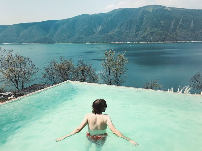 High angle view of man swimming in infinity pool against lake and mountain