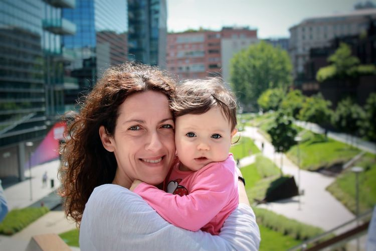 Portrait of mother and daughter in city