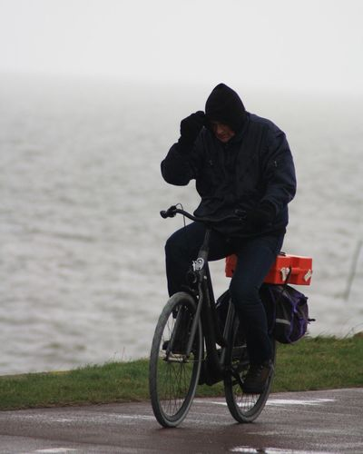 Man riding motorcycle on road against sea