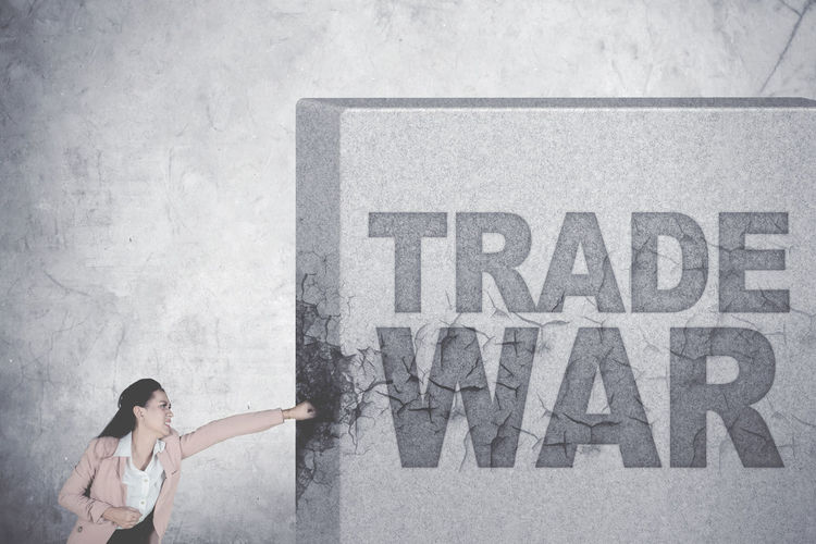 Digital Composite Image Of Businesswoman Punching Text On Wall