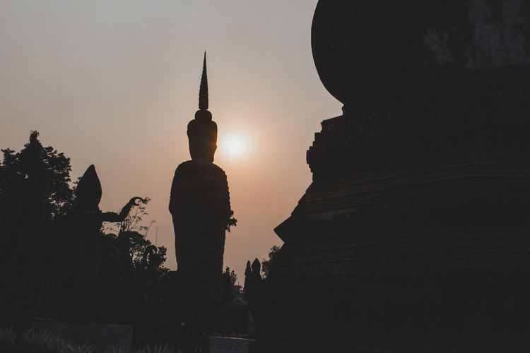 Silhouette of statue of building at sunset