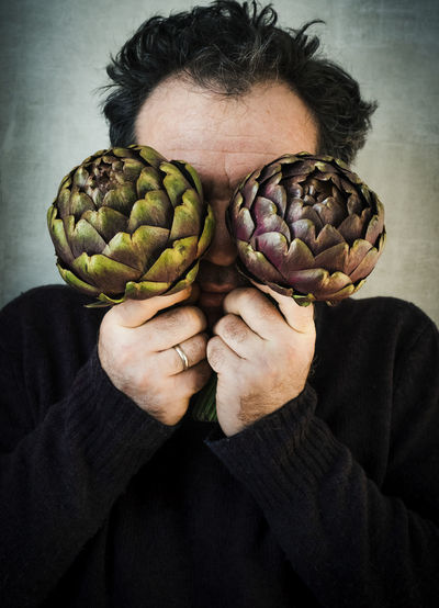 Close-up of man covering eyes with artichokes by wall