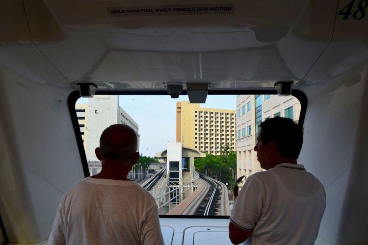 Rear View Of Men Sitting In Metro Train