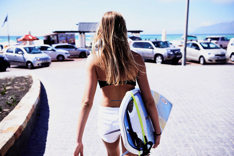 Rear View Of Woman Carrying Surfboard On Footpath