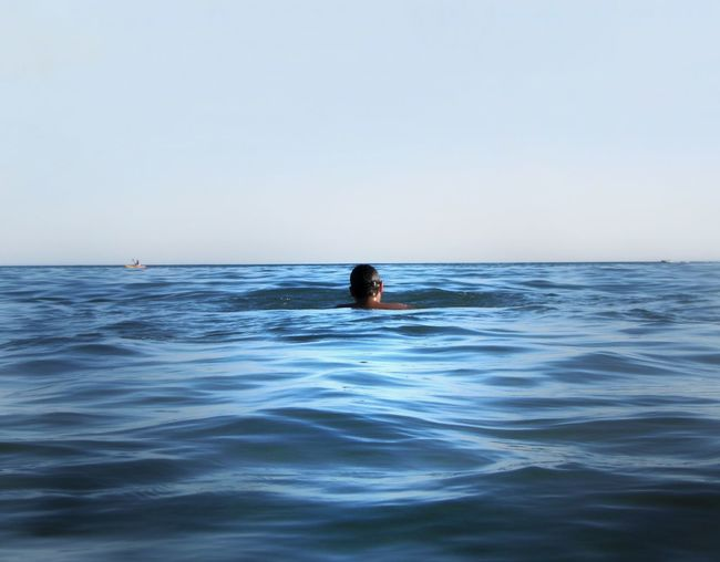 Rear view of person swimming in sea against clear sky
