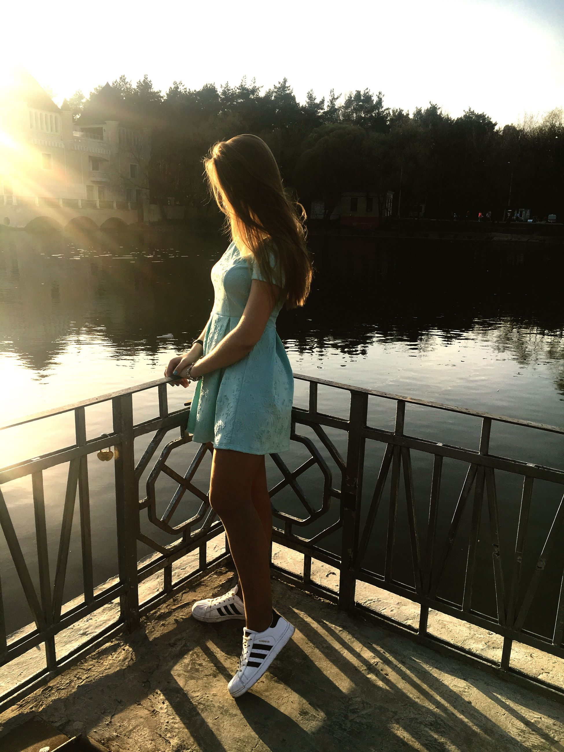 one person, real people, full length, standing, water, sunlight, river, casual clothing, leisure activity, outdoors, lifestyles, sunset, built structure, clear sky, day, women, nature, young women, young adult, sky, beauty in nature, tree