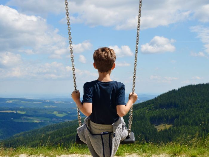 Rear view of boy swinging by landscape against cloudy sky