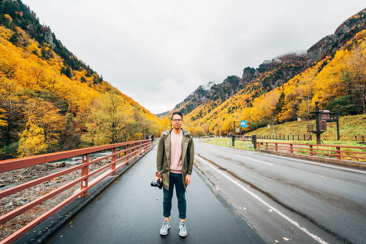 Daisetsuzan Transportation Full Length One Person Real People Autumn Sky Direction Road Standing Cloud - Sky Tree Day Nature The Way Forward Lifestyles Mountain Casual Clothing Plant Change Railing Diminishing Perspective Outdoors