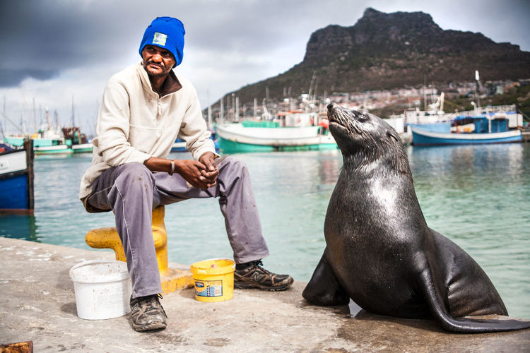 A sailor and his seal Sailor Sealife Seal Ocean Harbour Mountains Friends Southafrica Wildlife The Portraitist - 2014 EyeEm Awards Telling Stories Differently