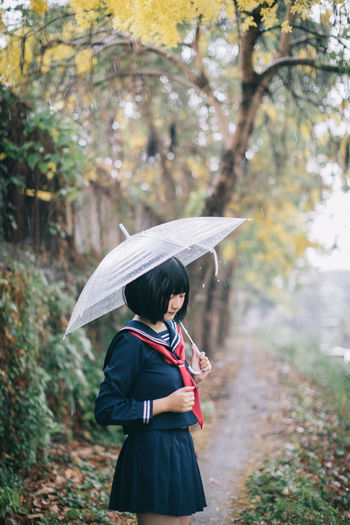 Woman with umbrella standing against trees during rainy season