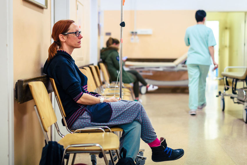 Patient sitting in hospital ward hallway waiting room with iv. Woman with intravenous therapy in her hand is waiting in the clinic corridor with blurred medical personnel in background. Cancer Hospital IV Intravenous Therapy Medicine Saline Ward Woman Catheter Chemotherapy Clinic Hand Hospital Ward Ill Infusion Bag Infusion Pump Infusion Set Infusions Intravenous Patient Patients Sick Sitting Treatment Waiting Room