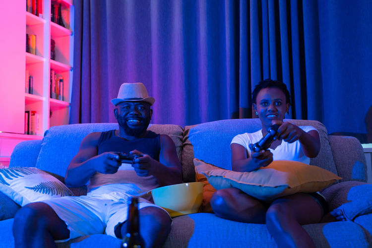 Happy African couple playing video games on console Couple Couple - Relationship Home House Love Togetherness Together Game Gaming Console Joystick African Happy Living Room Neon Sitting Furniture Sofa Indoors  Arts Culture And Entertainment Three Quarter Length Two People Lifestyles Leisure Activity Relaxation Men Front View Casual Clothing Holding Males  Adult Young Men People Mid Adult Mature Men Watching Tv Male Friendship Watching Video Games Games