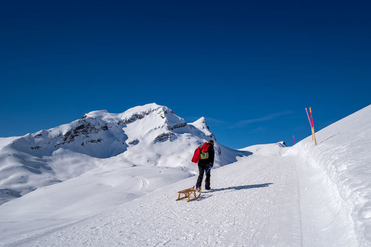 Rear view of woman walking with sled on snowcapped mountain