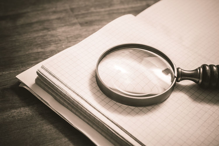 High angle view of magnifying glass with book on wooden table