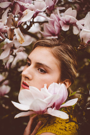Young Woman Amidst Pink Flowers During Springtime
