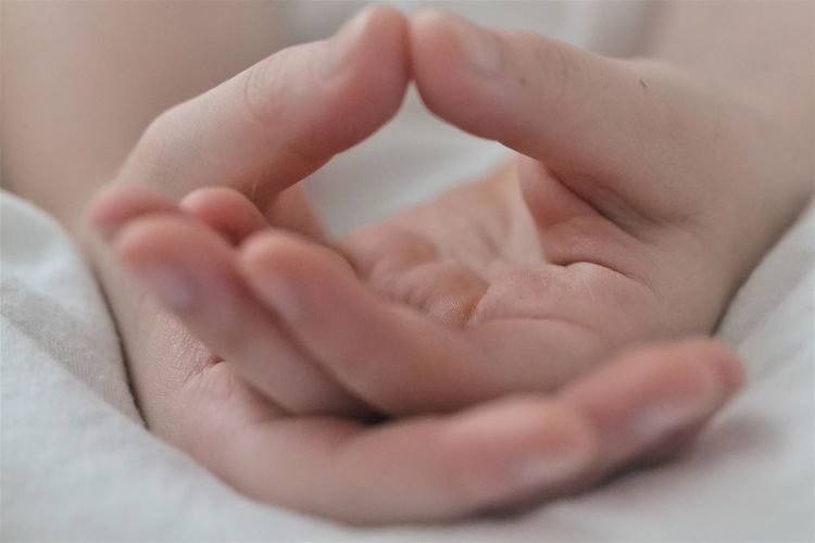 Close-up of baby hand on bed