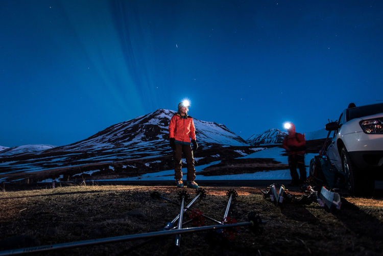 People standing on field against snowcapped mountain at night