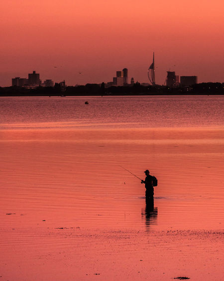 Rode to Hayling Island, and struggled to shoot much I was happy with, on riding home the sunset light hit and this guy waded out in to the sea and started fishing . . . . . . . . . . . . . . . . . . . . . . Canon 7D Mark2 and Canon 70-200mm f4L . . . . . . .. . . . . .. Fishing City Skyline Hayling Island  Orange Sky Portsmouth Portsmouth Harbour Sunset Silhouettes Tranquility Beauty In Nature cityscapes Fisherman Hampshire  Nature One Person Orange Color Scenics - Nature Silhouette Sky Skylines Solitude Sunset Sunset Light Sunsetporn Tranquil Scene Travel Destinations My Best Photo The Traveler - 2019 EyeEm Awards