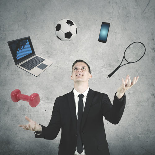 Digital Composite Image Of Businessman Juggling Personal Accessories Against Wall