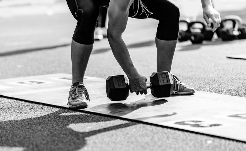 Low section of athlete exercising with dumbbells