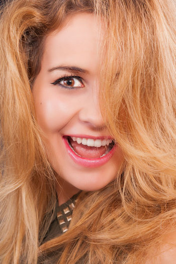 Close-up portrait of smiling young woman with blond hair