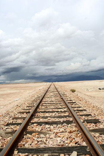Surface level of railway tracks against cloudy sky