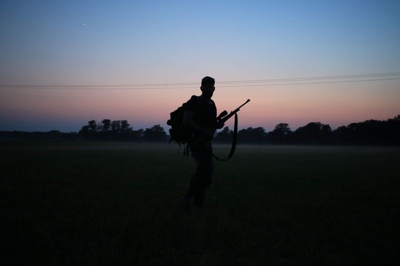 Silhouette Man With Rifle Walking On Field Against Sky During Sunset