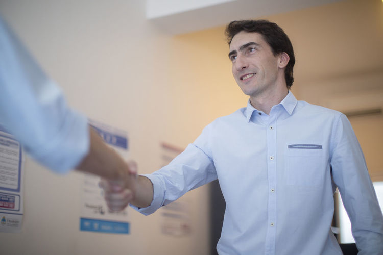 Business people shaking hands against wall